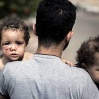 A Palestinian man holds his daughters Friday as he leaves al-Shifa Hospital in Gaza City. The two girls were treated for injuries sustained during a shelling attack by Israeli tanks. | AFP-JIJI