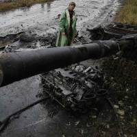 A Ukrainian soldier stands near a destroyed pro-Russian separatist tank just outside the eastern city of Slovyansk on Monday. | REUTERS