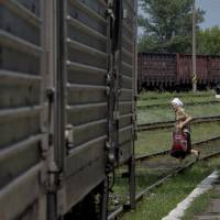 A woman looks at a refrigerated train loaded with the bodies of victims downed Malaysia Airlines Flight 17 on Sunday in Torez, eastern Ukraine. Armed pro-Russian separatists forced emergency workers to hand over all 196 bodies recovered from the crash site and had them loaded Sunday onto refrigerated train cars bound for a rebel-held city, Ukrainian officials and monitors said. | AP