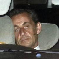 Former French President Nicolas Sarkozy arrives with authorities at the financial investigations unit of the police in Paris for questioning late Tuesday over suspicions he used his influence to secure leaked details of an inquiry into alleged irregularities in his 2007 election campaign. | REUTERS