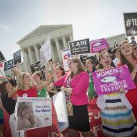 Demonstrators react to hearing the Supreme Court's decision Monday on the Hobby Lobby case outside the Supreme Court in Washington. The court says corporations can hold religious objections that allow them to opt out of the new health law requirement that they cover contraceptives for women. | AP