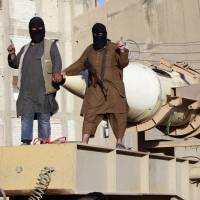 Militant Islamist fighters take part in a military parade in Syria's northern Raqqa province Monday. The fighters held the parade to celebrate their declaration of an Islamic caliphate after the group captured territory in Iraq, a monitoring service said. | REUTERS