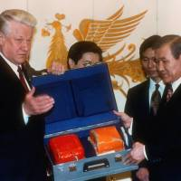 Russian President Boris Yeltsin (left) hands over the black box from Korean Airlines Flight 007, which was shot down by Soviet fighters in 1983, to South Korean President Roh Tae-woo at the presidential Blue House in Seoul in November 1992. | AFP-JIJI