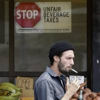 A man carrying a bottle of Coke walks past a store with a sign opposed to taxes on sugary drinks posted in San Francisco on Monday. | AP