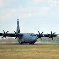 A U.S. Air Force C-130J Super Hercules from Ramstein Air Base, Germany, performs a grass landing during a training deployment at Powidz Air Base, in Poland.  The body of an adolescent boy was found in a wheel well of a similar US military plane after it landed in Germany over the weekend. | AFP-JIJI