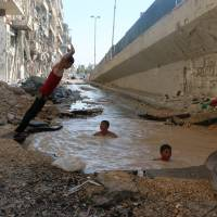 Syrian children play in a bomb crater flooded with water from a broken main in Aleppo on July 10. | AFP