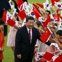 Chinese President Xi Jinping (right) and his South Korean leader Park Geun-hye greet children during a welcoming ceremony at the Presidential Blue House in Seoul on Thursday. | AP