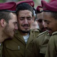 Israeli soldiers from the Paratroopers Brigade mourn over the grave of Sgt. Bnaya Rubel during his funeral at the military cemetery in Holon, Israel, on Sunday. Rubel was killed while fighting Palestinian militants in Gaza on Saturday.   AP