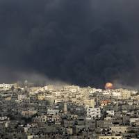 The flare of an explosion rises after an Israeli missile hits the smoke-enveloped Shejaia neighborhood of Gaza City in the northern Gaza Strip on Sunday. The neighborhood came under heavy tank fire Sunday as Israel widened its ground offensive against the Hamas militant group, causing hundreds of panicked residents to flee.   AP