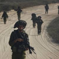 Israeli soldiers patrol outside the northern Gaza Strip on Tuesday, part of a mission to  find and destroy the warren of of Hamas tunnels that criss-crosses the border area.   REUTERS