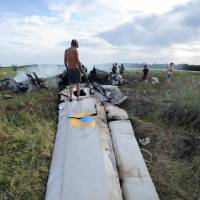 A man stands on the wreckage of a Ukrainian AN-26 military transport plane on Monday after it was shot down by a missile in the village of Davydo-Mykilske, east of Lougansk near the Russian border. | AFP-JIJI