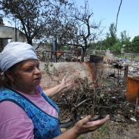 A woman stands outside her house, destroyed in one of the daily bombardments carried out by Ukrainian armed forces, in the village of Stanitsa Luganskaya, northeast of Lugansk, on Saturday. | AFP