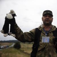 A pro-Russian separatist holds up a stuffed toy found at the crash site of Malaysia Airlines' Flight MH17 near the settlement of Grabovo, in eastern Ukraine's Donetsk region, on Friday. | REUTERS