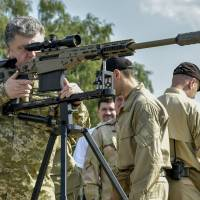 Ukrainian President Petro Poroshenko aims a rifle during a visit to a military base outside Kiev on Saturday. | REUTERS