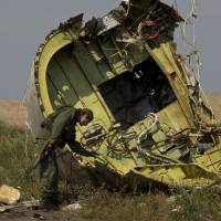 A pro-Russian rebel touches the wreckage of Malaysia Airlines Flight MH17 at the crash site near the village of Hrabove in eastern Ukraine on Tuesday. | AP