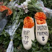 A message of sympathy for victims of the Malaysia Airlines Flight MH17 disaster is written on a wooden 'klomp,' traditional footwear that was worn by Dutch farmers, placed together with a bouquet of flowers in front of the Netherlands Embassy in Washington on Monday. | AP