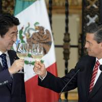 Mexican President Enrique Pena Nieto and Prime Minister Shinzo Abe make a toast during dinner at the National Palace in Mexico City on Friday. Abe arrived earlier in the day as part of a five-nation tour of Latin America and the Caribbean. | AFP