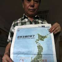 A man poses Wednesday in Chongqing, China, with a full page map with the headline 'Japan wants a war again' and showing mushroom clouds over Hiroshima and Nagasaki that was published in the July 3 issue of the Chongqing Youth Daily newspaper, days after Japan reinterpreted its war-renouncing Constitution to allow a greater military role. | AP