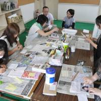 Volunteers clean photos salvaged from rubble left by the tsunami that wiped out Tohoku's coastline in March 2011, at a recent gathering in Kanie, Aichi Prefecture. | CHUNICHI SHIMBUN