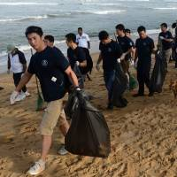 Crew members of the Japan Coast Guard vessel PLH 22 Yashima assist Sri Lankan counterparts as they help clean the beach at Mount Lavinia south of Colombo on Tuesday. The missions of the maritime law enforcement officers are not confined to guarding territorial waters. | AFP-JIJI