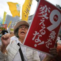 Protesters gather outside the prime minister's office in Tokyo on Tuesday, as the Cabinet prepared to authorize a historic reinterpretation of the Constitution to allow the right to collective self-defense. | AP