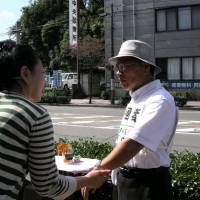 Residents of Omuta, Fukuoka Prefecture, participate in an annual training program related to dementia in which they practice how to approach confused people who are found wandering in the city, in September 2013. | OMUTA MUNICIPAL GOVERNMENT