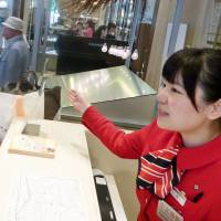 Qian Xiaolei helps foreign shoppers at the Mitsukoshi department store in Tokyo's Ginza district in May. | KYODO