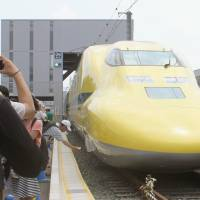 Railway fans take photos of the 'Doctor Yellow' shinkansen at a JR Tokai facility in Hamamatsu, Shizuoka Prefecture, last Sunday. | KYODO