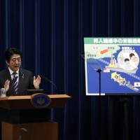 Prime Minister Shinzo Abe explains the Cabinet decision on Tuesday during a briefing for journalists at his official residence. The placard shows one scenario for how troops might protect Japanese nationals overseas. | REUTERS