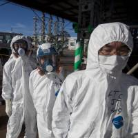 Workers in protective suits and masks wait to enter the emergency operation center at the crippled Fukushima No. 1 power plant in November 2011. A U.S. science advisory report says a key lesson from that crisis is that America's nuclear industry needs to focus more on worst case scenarios no matter how unlikely them may seem.   AP