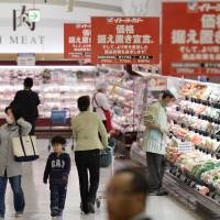 Banners declaring prices will be kept the same are displayed at a supermarket in Koto Ward, Tokyo, on April 1 this year, the day the consumption tax was raised to 8 percent. | KYODO