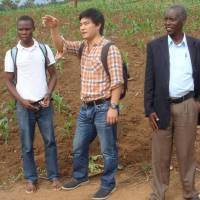 An aid initiative by Doga Makiura (center) in Rwanda addressed problems of hunger and oversupply of crops. The others here are his project partner (left) and a local farmer.   COURTESY OF DOGA MAKIURA