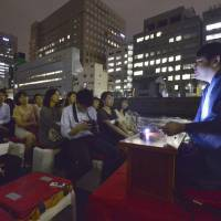 Professional storyteller Shunyo Kanda (right) narrates a ghost story aboard a boat, to people on a Hato Bus Co. tour, on July 18. | KYODO