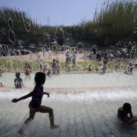 Children dip in a fountain at a park in Tokyo as soaring mercury across much of the nation prompted the Meteorological Agency to issue heat wave advisories Saturday for 41 of Japan's 47 prefectures. | AP
