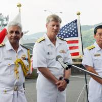 Maritime Self-Defense Force Rear Adm. Hidetoshi Iwasaki (right) joins Indian and U.S. naval officers at a news conference before the start of a weeklong joint exercise in the Pacific Ocean at the U.S. Navy's base in Sasebo, Nagasaki Prefecture, on July 24. | KYODO