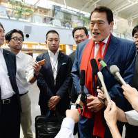 Antonio Inoki takes questions from reporters before departing from Beijing Capital International Airport for Pyongyang on Thursday.   KYODO
