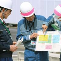 Kashiwazaki Mayor Hiroshi Aida (left) listens as Tokyo Electric Power Co. officials explain about an emergency power supply facility at Niigata Prefecture's Kashiwazaki-Kariwa nuclear power plant on May 9. | KYODO