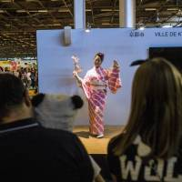 A Japanese woman dressed in a kimono performs a Japanese dance to promote the city of Kyoto at the 15th edition of the 'Japan Expo' exhibition devoted to Japanese culture and entertainment Tuesday in Villepinte, a Paris suburb. The event, which runs until Sunday, promotes Japanese culture, including manga, anime and video games.   AFP-JIJI