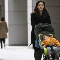 An employee at Nippon Yusen K.K. pushes a baby stroller during the morning commute in Tokyo's Marunouchi district. | BLOOMBERG