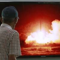 A man watches a TV news program showing a file picture of a missile launch conducted by North Korea, at Seoul Railway Station on Sunday. North Korea launched two projectiles presumed to be missiles into the sea the same day. | AP