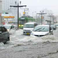 Drivers carefully navigate the flooded streets of Nagasaki on Thursday as heavy rain lashed western Japan. | KYODO
