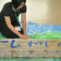 An official from the disaster-hit village of Tanohata in Iwate Prefecture touches a signboard that was swept away in the March 11, 2011, tsunami. The sign was returned to the village on Friday. | KYODO