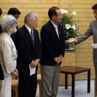 Prime Minister Shinzo Abe receives a petition abduction groups at his official residence in Tokyo on July 4. There is speculation that Abe could use a possible breakthrough on the emotive issue to call a snap election. | REUTERS
