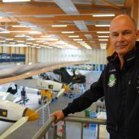 Bertrand Piccard overlooks the Solar Impulse 2 aircraft in Payerne, Switzerland, on June 11. He plans to pilot the airplane around the world to show that renewable energy can be more useful than nuclear power.   KYODO