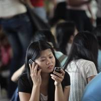 A Filipino domestic helper talks on her cellphone in central Hong Kong. Japan, like Hong Kong, is considering bringing in foreigners as domestic laborers in a bid to push more women, many of whom quit their jobs after marrying and becoming mothers, to return to the workforce. | BLOOMBERG NEWS