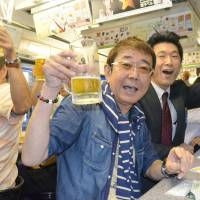 Passengers enjoy mugs of draft beer Thursday aboard a special Nagasaki streetcar that runs around the city serving beer and other beverages. The popular service is already fully booked through its last ride of the year on Sept. 20. | KYODO