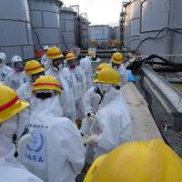 Members of the International Atomic Energy Agency inspect a spent fuel pool at the Tokyo Electric Power Co.'s crippled Fukushima No. 1 nuclear power plant in Okuma, Fukushima Prefecture, last November. | AFP