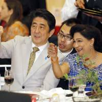 Prime Minister Shinzo Abe and Trinidad and Tobago Prime Minister Kamla Persad-Bissessar (right) talk at a dinner party in Port-of-Spain. | KYODO