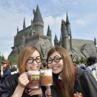 Visitors dressed as characters from the 'Harry Potter' book and movie series pose outside the newly opened Wizarding World of Harry Potter at Universal Studio Japan in Osaka on Tuesday. | KYODO
