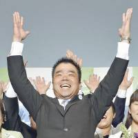 Taizo Mikazuki raises his arms and shouts 'Banzai!' on Sunday in Otsu after media outlets reported he was set to be elected as Shiga Prefecture's next governor.  | KYODO